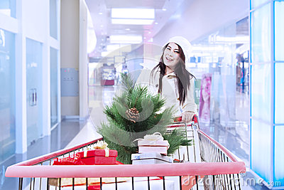 Trole da compra do impulso da mulher com árvore de Natal