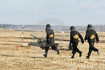 Troopers run to a tank