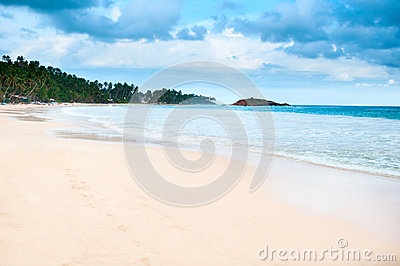 Tropical beach with cloudy dark blue sky