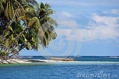Tropical beach with a dugout canoe