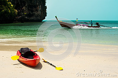 Tropical beach landscape with red canoe boat at ocean