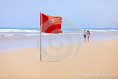 Tropical beach and a red flag. Do not swim!
