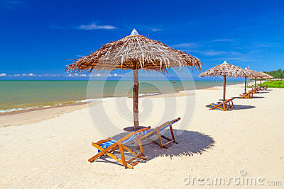 Tropical beach scenery with parasol and deck chairs
