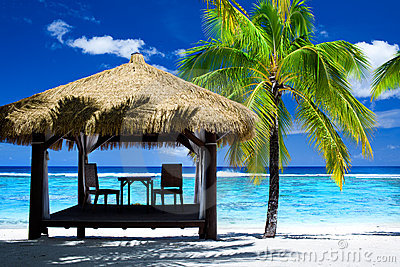 Tropical gazebo with chairs on amazing beach