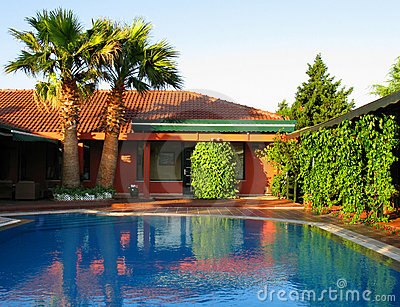 tropical house with palms and swimming pool