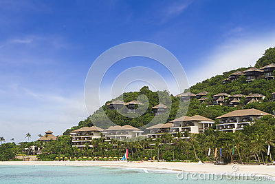 Tropical sea, beach and hotel on sky background