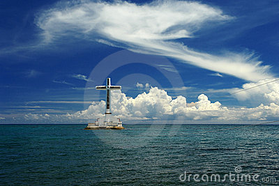 Tropical seascape with cross and clouds.