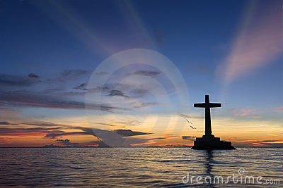 Tropical sunset with cross silhouette.