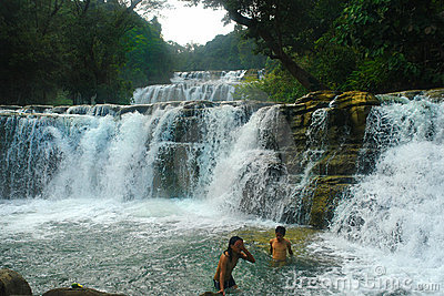 Tropical waterfall, swimming boys.
