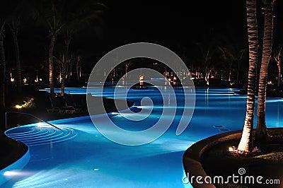 Tropischer Rücksortierung-Swimmingpool an der Nachtzeit