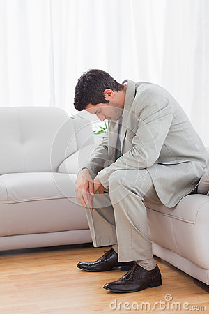 Troubled buinessman sitting on sofa lowering his head