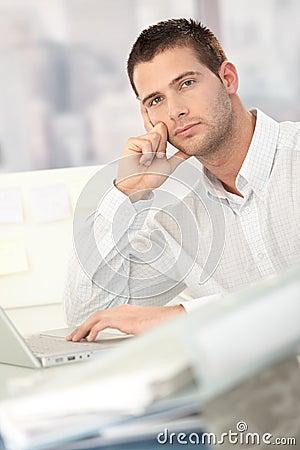 Troubled businessman sitting at desk