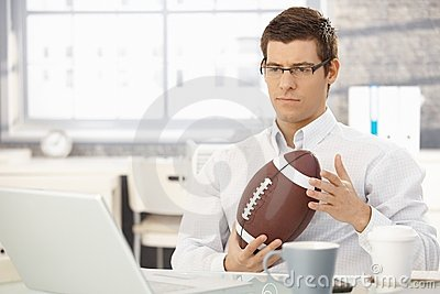 Troubled businessman thinking holding football