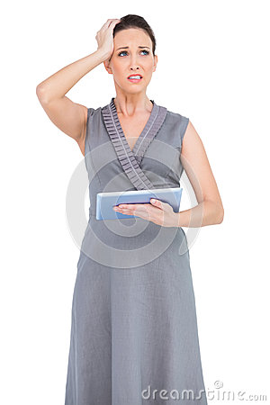 Troubled gorgeous woman holding digital tablet