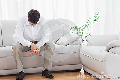 Troubled young man sitting on sofa
