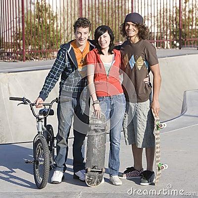 Três adolescentes no skatepark