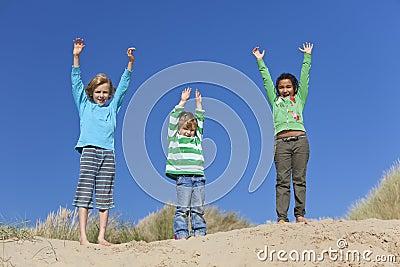 Três braços das crianças levantados tendo o divertimento na praia