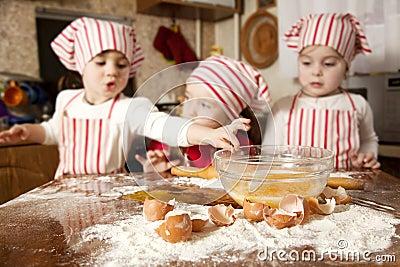 Três cozinheiros chefe pequenos na cozinha