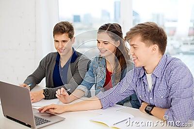 Três estudantes de sorriso com portátil e cadernos