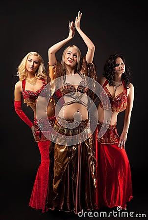 Três raparigas dançam no traje árabe