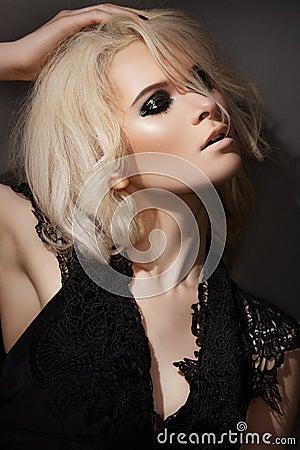 Trucco di modo. Modello biondo sexy in vestito nero