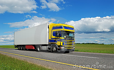 Truck with blue-yellow cabin moving on highway.