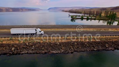 Truck crossing Columbia river with canyons in background. Sweeping aerial of a semi truck crossing the Columbia river with canyon hills in background on a bright