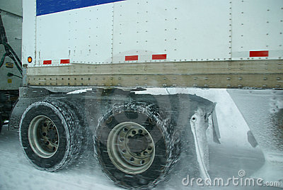 Truck tires spinning on highway during snowstorm