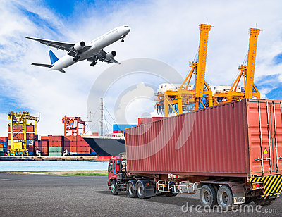 Truck transport container and cago plane flying above ship port Stock Photo