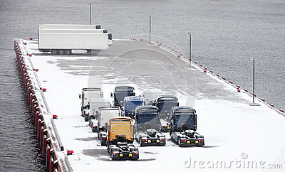 Trucks and trailers waits on snowbound pier