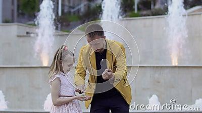 Truco mágico de la demostración del ilusionista con las bolas a una niña almacen de metraje de vídeo