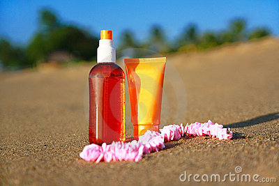 Tubes with sunblock and bread on sand on beach
