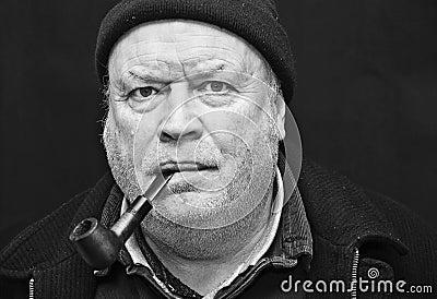 Tubulação de fumo do homem idoso
