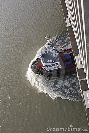 A Tug Boat Passes Beneath a Bridge