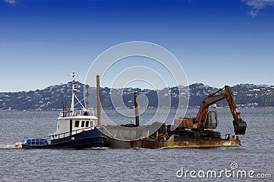 Tug boat pushing dredging barge