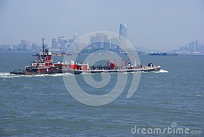 Tugboat pushing barge in New York Harbor,