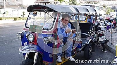 Tuk tuk driver o auto rickshaw juega al teléfono mientras espera un nuevo pasajero Bangkok, Tailandia - Diciembre de 2002 almacen de metraje de vídeo