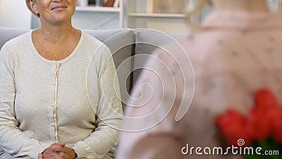 Tulipanes de ocultación de la niña para sorprender a la abuelita de amor el 8 de marzo, visita del fin de semana almacen de metraje de vídeo