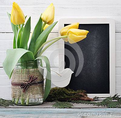 Tulips bouquet with blank blackboard