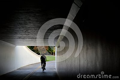 A bicycle rider on the Boise Greenbelt emerges from the dark tunnel beneath Capitol Boulevard and into Julia Davis Park.