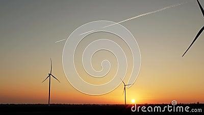 Turbines de vent au beau coucher du soleil contre le contexte d'un vol d'avion dans le ciel, partant d'une traînée banque de vidéos
