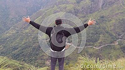 Turista del giovane con lo zaino che sta sull'orlo di bello canyon e delle mani victoriously sollevate Viandante maschio archivi video