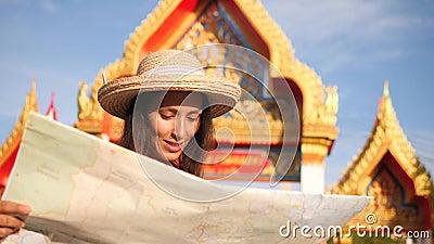 Turista joven de la raza mixta en el mapa de Straw Hat Woman Holding City y el templo budista tailandés de exploración Phuket, Ta almacen de metraje de vídeo