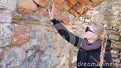 Turista olha para um muro de pedra no castelo antigo video estoque