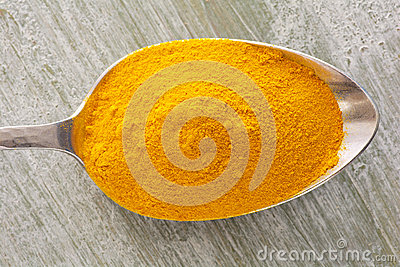 Turmeric powder on a spoon Stock Photo
