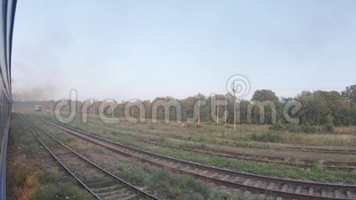 Turn of the train on nature. UKRAINE, BERDYANSK - Jule 19, 2019: View from the car on the turn of the train and a smoking locomotive of Berdyansk in Jule 2019 in stock footage