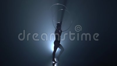 Turner dreht das Band auf ihren Armen und hebt ihr Bein oben an Langsame Bewegung Rauchen Sie Hintergrund Schattenbild stock video