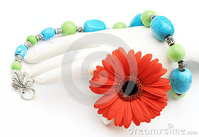 Turquoise necklace over hand with red orange daisy