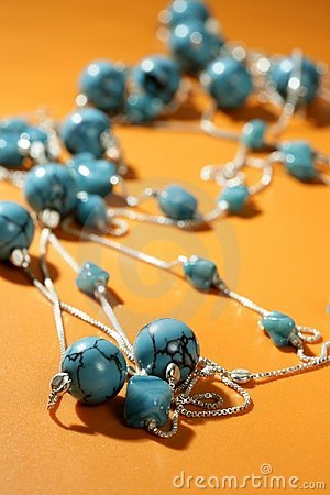 Turquoise necklaces over orange background