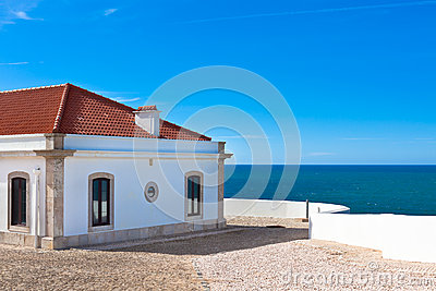 Turquoise sea, blue sky and white house in Portugal